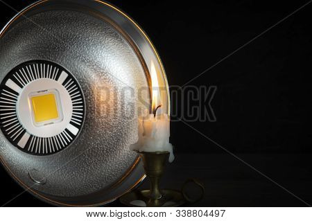 Turned Off Led Strobe Light With Reflector Pointing At Burning Candle On Vintage Candlestick, Viewed