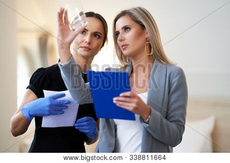 Adult chambermaid and hotel manager cleaning the room