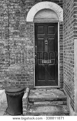 A Plastic Trash Bin Is Standing By An Old Door In London, England. The Brick Wall Has Seen Better Da