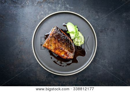 Minimalistic design Japanese salmon fish filet with avocado and wasabi creme glazed in teriyaki sauce as closeup on a modern design plate