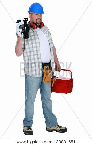 Tradesman holding a circular saw and his toolbox poster