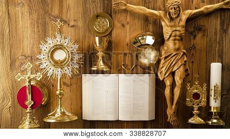 Catholic Religion Symbols. The Cross, Monstrance, Jesus Figure, Holy Bible And Golden Chalice On The