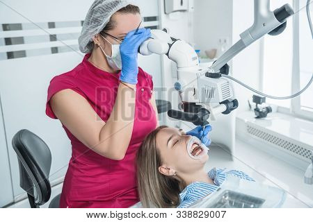 The Dentist Examines The Patient With A Microscope In The Dentists Office