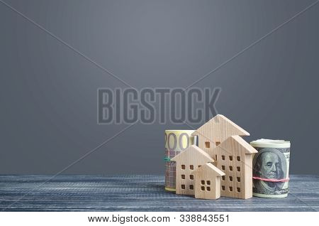 Residential Buildings And Money Bundle Rolls. House Maintaining Cost, Utility Bills. Modernization H