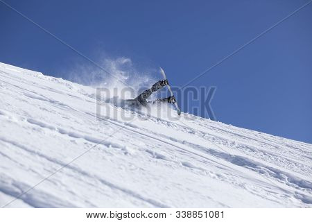 Snowboarder Dressed In Sportswear, Helmet And Glasses Falls On The Slopes During The Descent In Fres