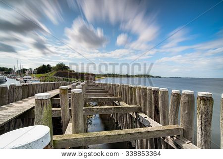 Dynamic Moving Exaggerated White Clouds Against A Blue Sky Above A Dutch Lake Near An Old Seaport