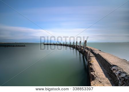 Weathered Concrete Breakwater With A Rusty Sheet Pile And Angled Wooden Beams Reflected In The Mirro