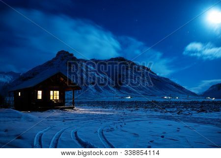 Landscape with a wooden house with light from the window in a winter night.  Scenic view of moonlight on the snow with mountains in the background. South Iceland.