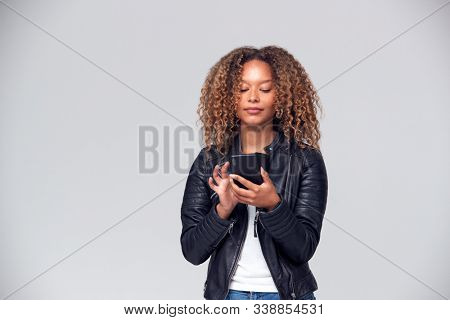 Studio Shot Of Woman Wearing Leather Jacket Using Mobile Phone