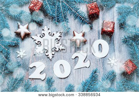 New Year 2020 background with 2020 figures, Christmas toys, blue fir tree branches and snowflakes. New Year 2020 festive still life, New 2020 year composition