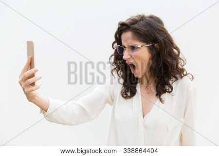 Furious Exaggerated Woman In Glasses Staring At Phone Screen With Open Mouth. Wavy Haired Young Woma