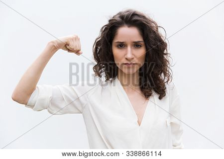 Confident Serious Woman Flexing Bicep, Showing Hand Muscle. Wavy Haired Young Woman In Casual Shirt