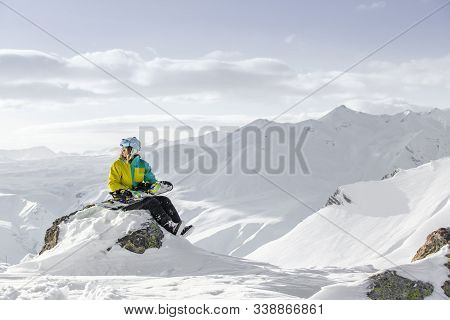 Girl In Snowboard Suit Sitting On The Snow At The Top Of The Mountain And Looking Into The Distance.