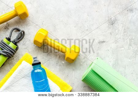Gym Equipment - Dumbbells, Jump Rope - Frame On Grey Background Top-down Copy Space