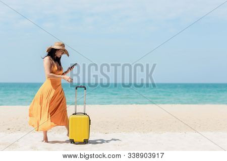 Asian Women Traveler Holding Yellow Luggage Walking And Check In Smart Phone On The Beach. Traveler