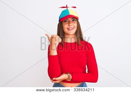 Young beautiful girl wearing fanny cap with propeller standing over isolated white background smiling with happy face looking and pointing to the side with thumb up.