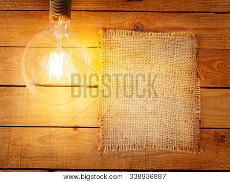 Piece of old canvas. Hanging incandescent lamp on wooden wall. Edison type bulb. Space for text.