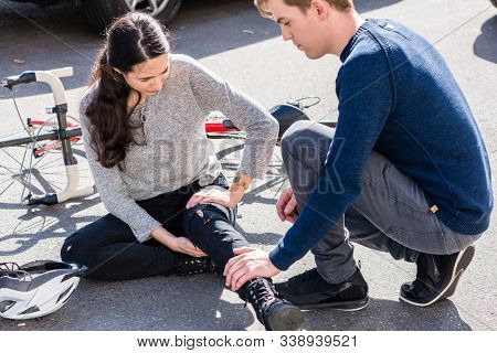 Helpful young man giving first aid to an injured young woman after suffering a painful strain or fracture in bicycle accident on the street