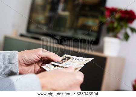 BARCELONA, SPAIN - DESEMBER 11, 2019: Closeup of a man with some tickets of the Spanish Christmas Lottery in his hand while is watching the televised drawn in the TV