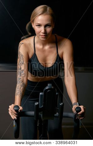 Young Confident Woman Athlete Exercising On Bicycle Indoors. Attractive Determined Fitness Girl Doin