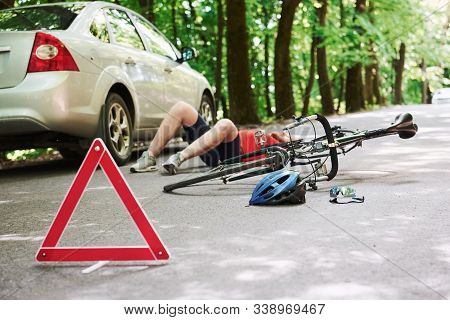 Man Lying Down. Victim On The Asphalt. Bicycle And Silver Colored Car Accident On The Road At Forest