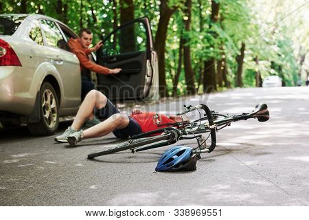 Driver Opening The Door. Victim On The Asphalt. Bicycle And Silver Colored Car Accident On The Road