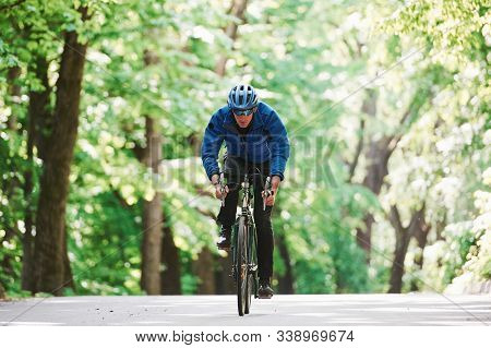 Stamina And Strength. Cyclist On A Bike Is On The Asphalt Road In The Forest At Sunny Day.