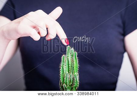Female Hand With Red Nail Polish And Green Cactus. Ouch. Prickly Prick. Dangerous Touch Concept. Bla