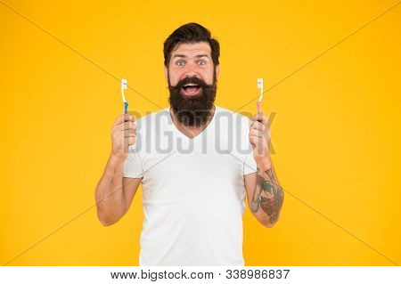 Mouth Matters. Bearded Man Happy Smile With Toothbrushes. Happy Hipster Hold Brushes Yellow Backgrou