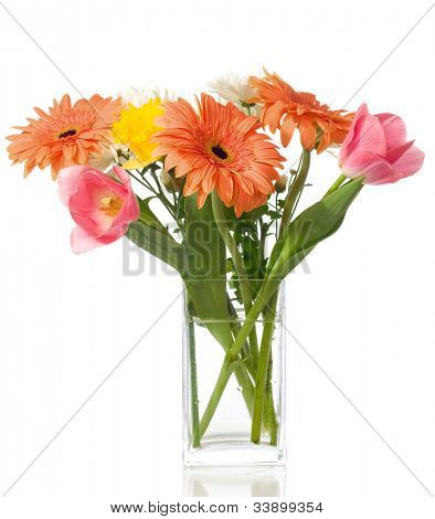 bunch of gerberas and tulips in the transparent vase on the white background