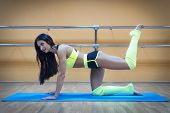 A beautiful athletic girl in the kneeling position doing leg exercises at gymnastic hall background. Dancer dressed in a sporty uniform stretching and exercising on mat. Attractive brunette knelling. poster