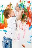 Three year old boy painting the wall and having a lot of fun poster