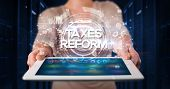 Young business person working on tablet and shows the inscription: TAXES REFORM, business concept poster