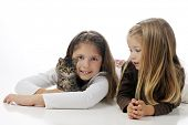 Sisters laying on the floor cuddling their kitty.  On a white background. poster