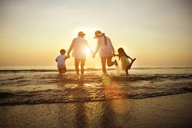 Summer Vacations. Happy Family Is Holding Hands Running On The Beach At Sunset. Father And Mother An