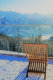 Lounging In The Alps. A Single Lounge Chair In The Snow To Enjoy The Spectacular Mountaintop View Fr