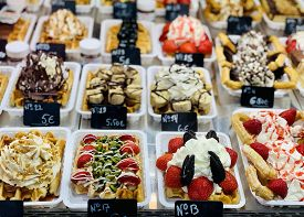 Belgian Waffles. A Tempting Selection Of Fresh Belgian Waffles Topped With Chocolate, Fruit And Crea