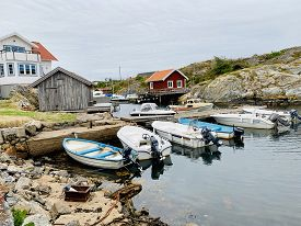 July 31, 2019 - Skärhamn, Sweden. Swedish Beach House. Boats In A Small Harbor In Front Of A Traditi