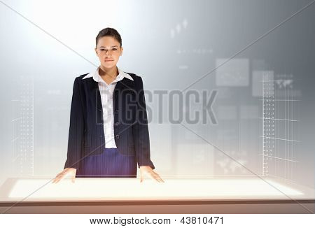 Image of young businesswoman standing against high-tech picture background