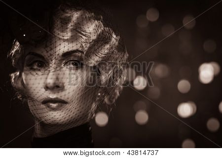 Toned picture of  elegant blond retro woman   wearing little hat with veil