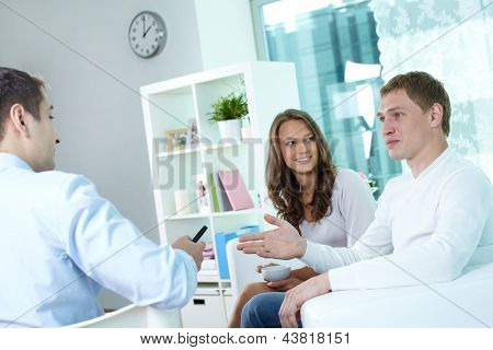 Young couple discussing their actuarial plan with an insurance broker