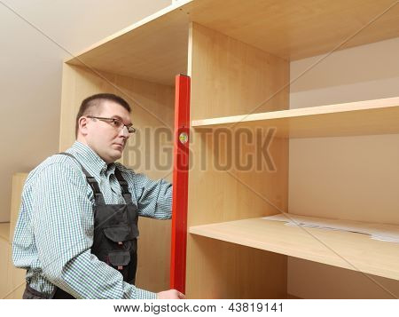 Carpenter assembling wardrobe furniture in walk-in closet