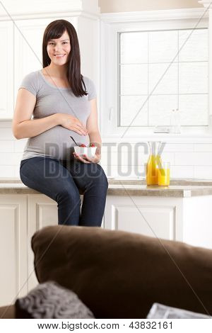 Happy smiling pregnant woman at home in kitchen with healthy snack