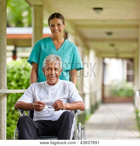 Senior man in wheelchair with nurse on a stroll through the hospital garden