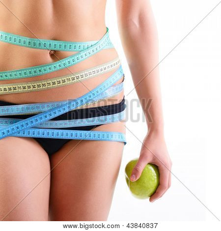 Beautiful slim woman holding green apple and with several color measuring tapes on her waist, over white