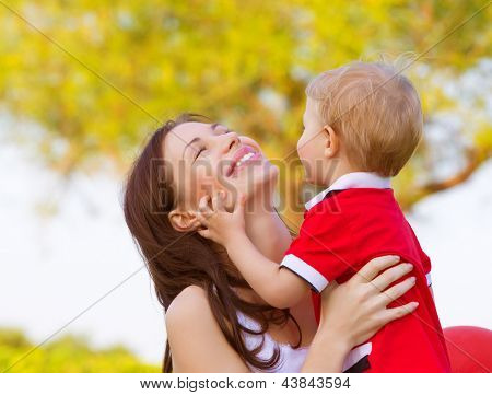Happy young mother playing game with cute little son outdoors in spring time, cheerful child with mom having fun on backyard, woman with small kid resting in the park in sunny day
