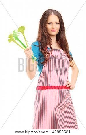 Young woman wearing red apron and holding plastic spoons isolated on white background
