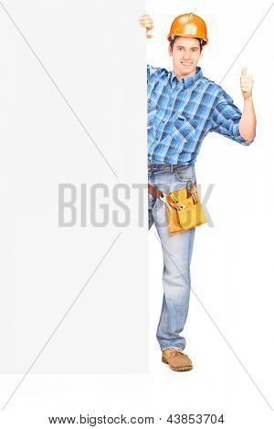 Full length portrait of a male worker with helmet posing behind a blank panel and giving thumb up isolated on white background