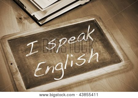 sentence I speak english written with chalk on a blackboard, on a table with books