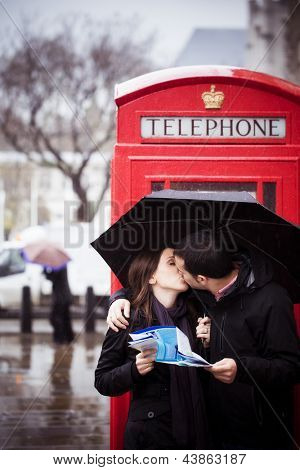 Sweet honeymoon couple kissing instead of consulting map in London
